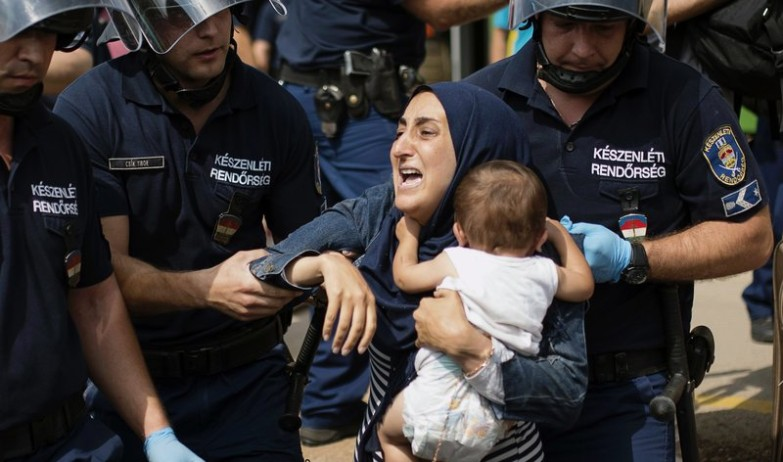 A migrant family is arrested by local police after their local train coming from Budapest and heading to the Austrian border has been stopped in Bicske, west of the Hungarian capital on September 3, 2015. The train carrying between 200 and 300 migrants left Budapest's main international train station after authorities re-opened the station to migrants as the EU is grappling with an unprecedented influx of people fleeing war, repression and poverty in what the bloc has described as its worst refugee crisis in 50 years. AFP PHOTO / ISTVAN BIELIK 4638#Agencia AFP